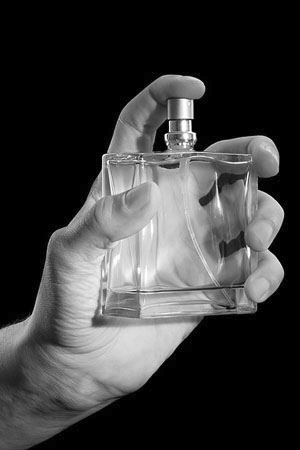 man holding a cologne bottle